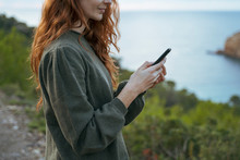 Redheaded Young Woman Using Ce...