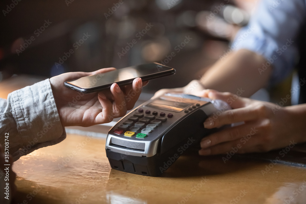 Fototapeta Client paying on terminal using smartphone nfc method