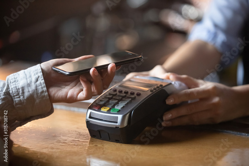Fotografia Client paying on terminal using smartphone nfc method