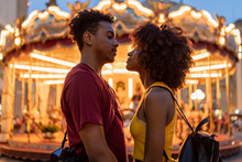Affectionate Young Tourist Couple At An Illuminated Carousel In The City At Dusk, Florence, Italy
