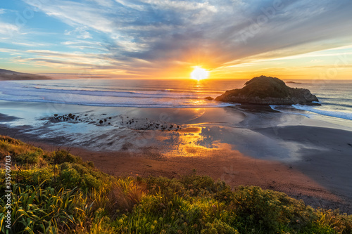 New Zealand, Tongaporutu, Clouds over sandy coastal beach at sunset with Motuotamatea island in background - 315709703