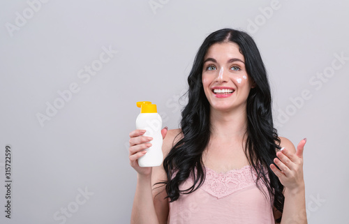 Fotografía  Young woman with sunscreen on a gray background