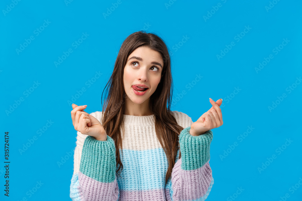 Fototapeta Dreamy and sassy good-looking thoughtful woman imaging lots of valentines day presents, licking lips tempting, looking up pondering, showing korean hearts sign, standing blue background