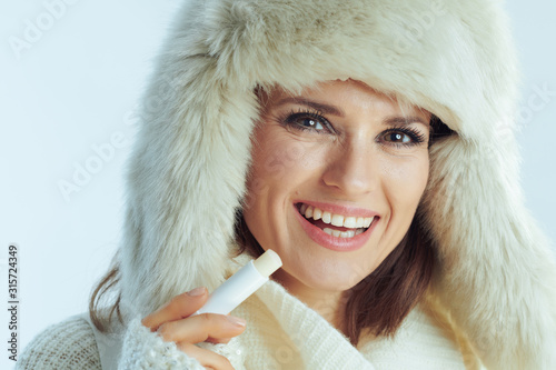 Fotografía  woman using hygienic lipstick on winter light blue background