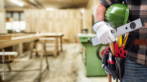 Fototapeta Close-up. Carpenter with hands protected by gloves holds helmet and level. Construction industry, carpentry workshop. obraz