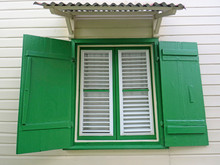 White Wooden Window, Green Shutters And Sheet Roof On The Exterior Of A White House. Vintage Green Window Shutters. Caribbean Architecture