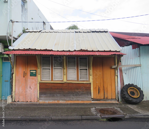 Photo Caribbean wooden house with orange doors, tin roof and closed white window shutters