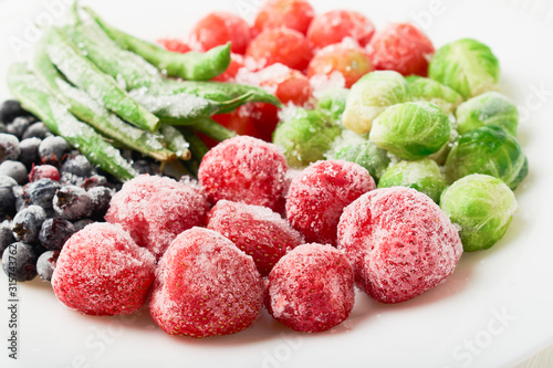 Obraz White plate with frozen food in a plate - strawberries with shadberry and brussels sprouts with asparagus beans - fototapety do salonu