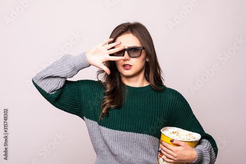 Платно Scared young girl in 3d imax glasses covering face with palm, watching movie film, holding bucket of popcorn isolated on white background