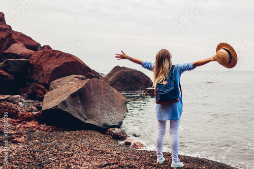 Ταπετσαρία τοιχογραφία Woman traveler walking raised arms feeling happy on Red beach in Santorini island, Greece
