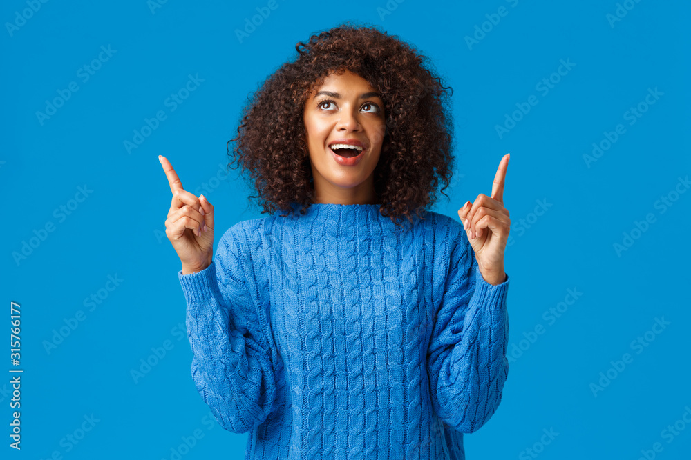 Fototapeta Cheerful amused african-american girl celebrating with friends new year, happy holidays, looking fireworks with excited smile, pointing looking up astonished and joyful, standing blue background
