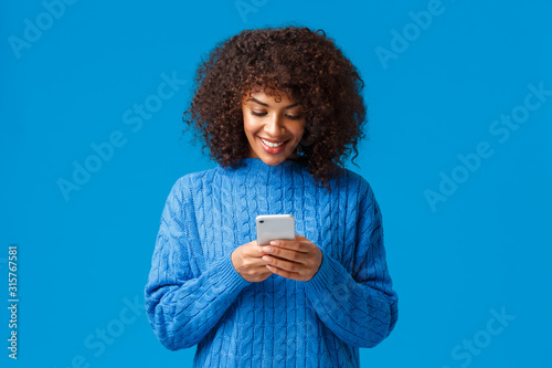 Carefree relaxed attractive african-american lovely woman, answering boyfriend on phone, chatting writing message using smartphone, looking mobile screen and smiling, wear winter sweater