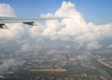 View From The Plane To The Wing, Beautiful Clouds, The City Below And The Sky.