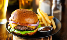 Cheeseburger And Fries On Plate Served With Beer At Restaurant