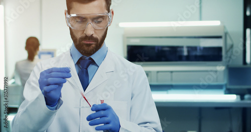 Obraz Caucasian young man laboratory scientist in glasses making a blood test with a tube in hands. Portrait. Close up - fototapety do salonu
