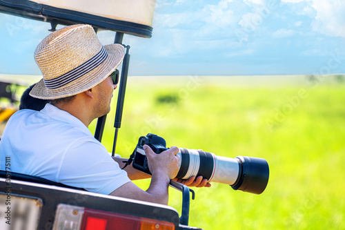 The man photographer takes a picture from touristic vehicle on tropical safari Canvas Print