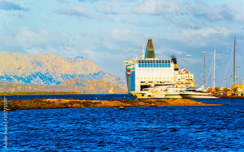 Harbor with ferry ship at Mediterranean Sea in Old city of Olbia on Sardinia Island in Italy Wallpaper Mural