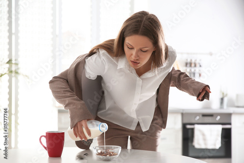 Young woman cooking breakfast in hurry at home. Morning preparations