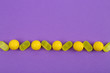 canvas print picture - Delicious lemon candies on purple background, flat lay