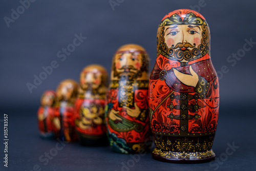 Fotografia, Obraz Traditional Russian matryoshka dolls lined up against gray background, doll with