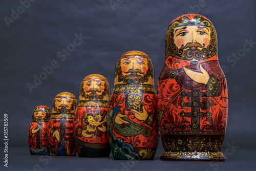 Obraz na plátne Traditional Russian matryoshka dolls lined up against gray background, doll with