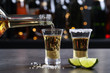 canvas print picture - Pouring Mexican Tequila from bottle into shot glass on bar counter