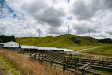 Rural Agricultural View Of A Sheep Farm And Its Sheep And Cattle Yards On The  Hills And Valleys With Electricity Generating Wind Turbines On The Peaks