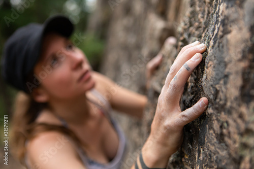 A close up and selective focus view as a young caucasian lady scales a limestone Canvas Print