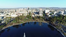 Aerial Descent Over Deep Blue MacArthur Park Lake Fountain, Flying West, With City Background