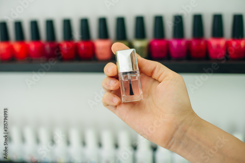 Cuadros en Lienzo  girl holds nail polish on the background of nail polishes