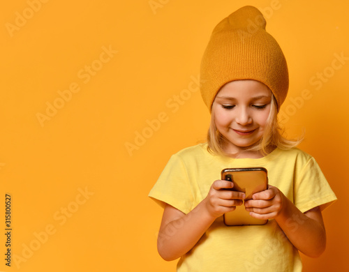 Obraz Little blonde kid dressed in t-shirt and hat, posing with smartphone against yellow background. Technology, children, internet. Close-up shot - fototapety do salonu