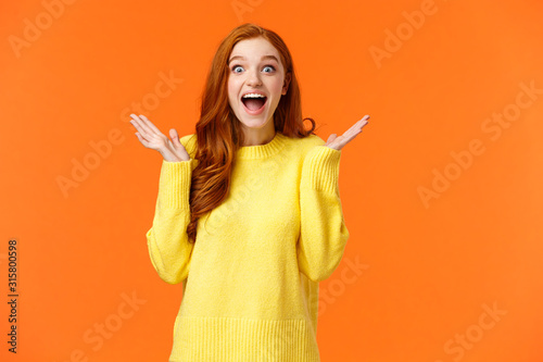 Obraz Holidays, surprise and fashion concept. Happy cheerful redhead female customer shopaholic, excited see christmas sales, smiling amused, clap hands from thrill and joy, standing orange background - fototapety do salonu