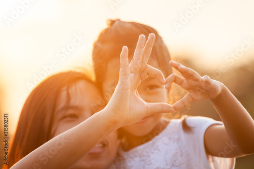 Obraz Asian mother and daughter making heart shape with hands together with love in the field with sunlight - fototapety do salonu