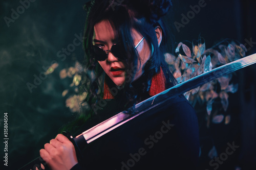 Oriental style girl with katana sword on dark smoky background in shallow depth Fotobehang