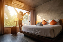 Tourist Woman Raised Her Hands With Her Luggage In Hotel Bedroom.