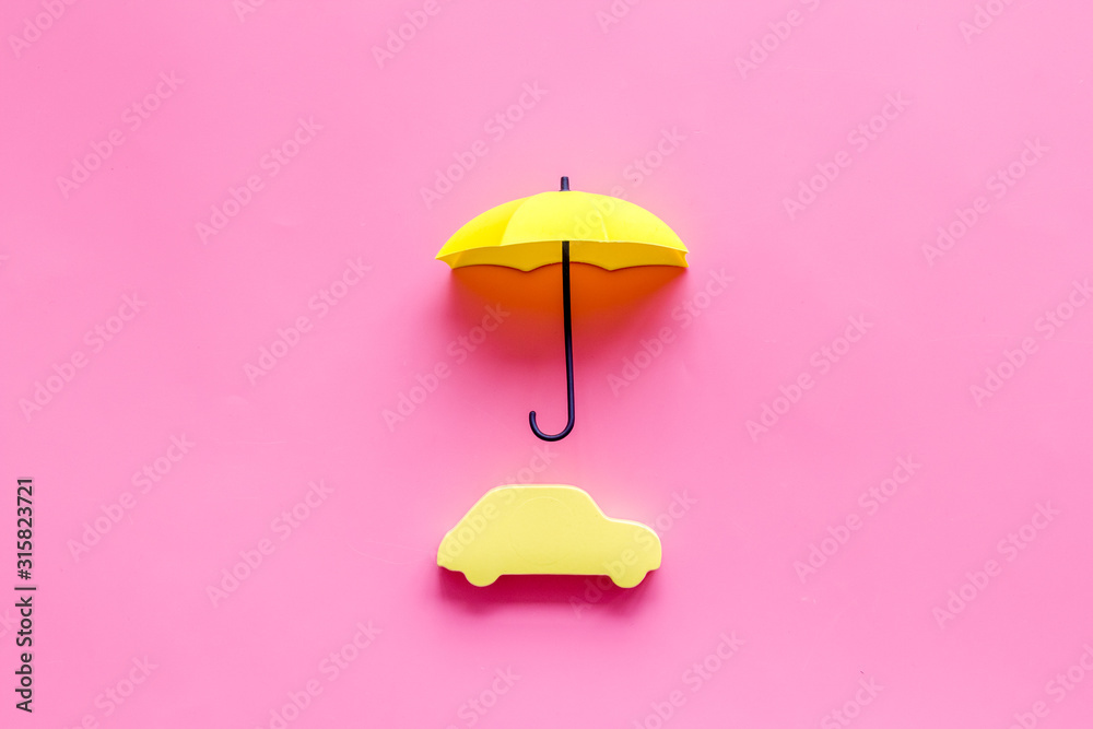 Fototapeta Car insurance. Automobile toy under umbrella on pink background top-down copy space