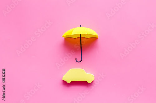 Car insurance. Automobile toy under umbrella on pink background top-down copy space