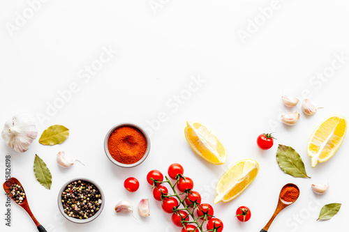 Obraz Kitchen frame with spices and food - pepper, garlic, cherry tomatoes - on white background top-down frame copy space - fototapety do salonu