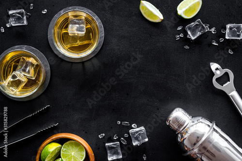 Fotografia Bar background with whiskey, ice and shaker on black desk top-down frame copy sp