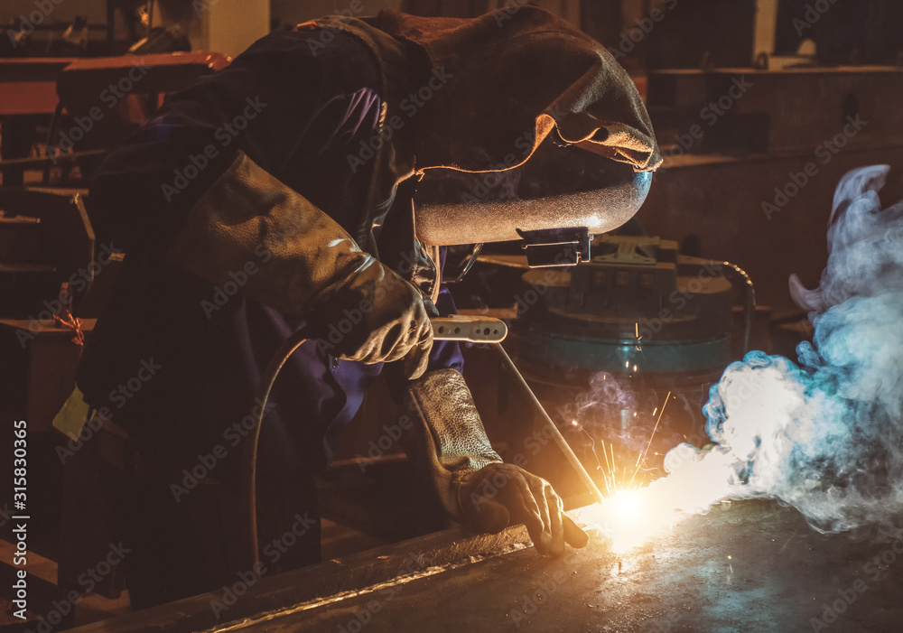 Fototapeta Industrial Worker labourer at the factory welding steel structure