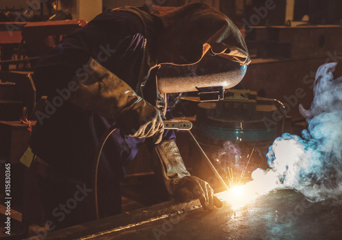 Industrial Worker labourer at the factory welding steel structure Canvas Print