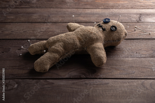 Photo Voodoo doll on a wooden background with dramatic lighting