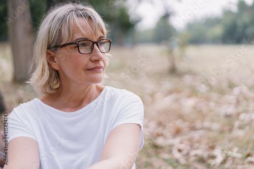 Fototapeta Elderly women caucasian  wear glasses while sitting  think at the public park in the autumn obraz