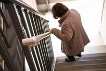 階段を降りている高齢...