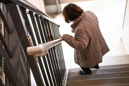 Obraz na plátně 階段を降りている高齢女性