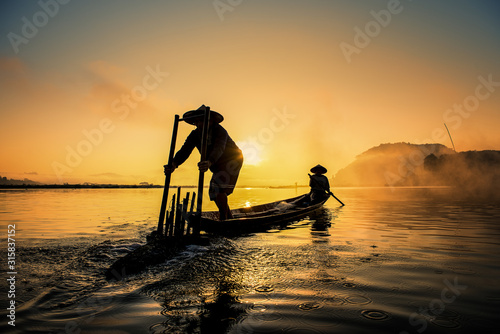 Obraz Asian Fishermen on boat fishing at lake, Thailand countryside - fototapety do salonu
