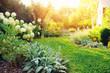 Leinwandbild Motiv summer private garden with blooming Hydrangea Annabelle. Curvy lawn edge, beautiful pathway. Landscape design in English cottage style.