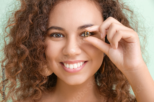 Fototapeta Young woman with fish oil on color background, closeup obraz