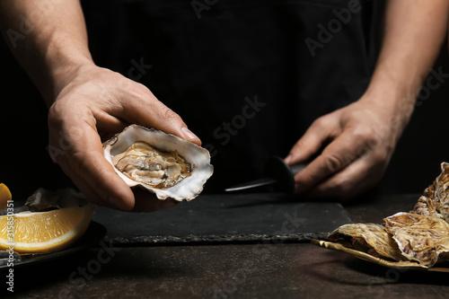 Man opening shell of fresh oyster on dark background Wallpaper Mural