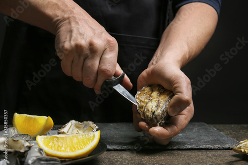 Man opening shell of fresh oyster on dark background Canvas Print